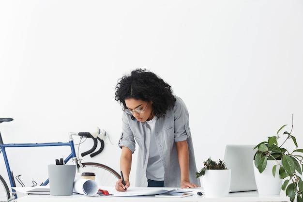 Attraktiver stilvoller weiblicher chefingenieur der gemischten rasse in runden gläsern, die über ihrem weißen schreibtisch stehen