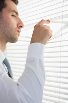 Attraktiver strenger geschäftsmann, der durch rollo ausspioniert