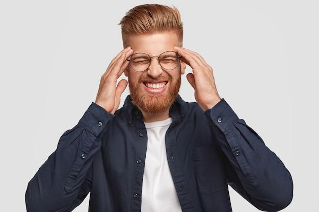 Attraktiver, stressiger, fuchsiger mann beißt die zähne zusammen, hält die hände an den schläfen, hat kopfschmerzen, ist in modische kleidung gekleidet und über der weißen wand isoliert. menschen, emotionen und gefühle