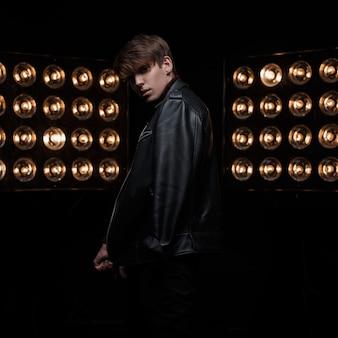 Attraktiver süßer junger stilvoller kerl in einer kühlen schwarzen vintage-lederjacke in der schwarzen hose, die in einem dunklen studio vor dem hintergrund der professionellen leuchtend orangefarbenen lampen posiert. fashion man star