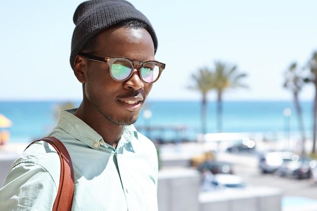 Attraktiver tourist, der im freien posiert, während er sehenswürdigkeiten und orte des ferienortes erkundet