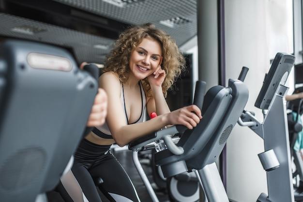 Attraktiver trainer der jungen frau, der auf laufband im fitnessstudio läuft