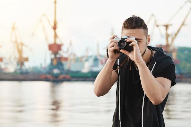 Attraktiver typ, der mit kamera arbeitet. junger stilvoller fotograf, der durch kamera während fotosession mit herrlichem modell schaut, bilder im hafen nahe der küste macht, sich auf arbeit konzentriert
