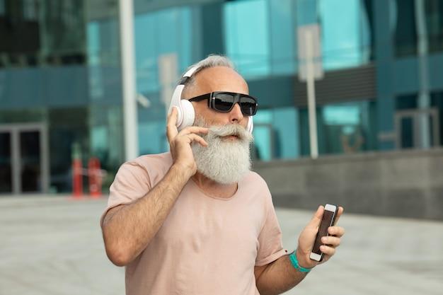 Attraktiver und lächelnder bärtiger alter älterer mann mit weißem haar, der musik vom smartphone im freien trägt, das weiße kopfhörer trägt.