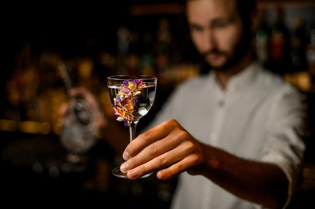 Attraktiver unscharfer barmixer, der ein cocktail im glas verziert mit blumen dient