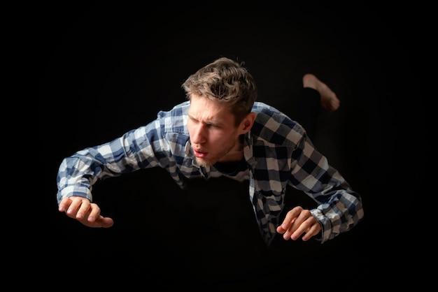 Attraktiver verängstigter mann fällt aus der höhe auf dunklem hintergrund b