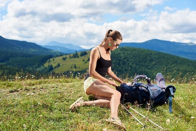Attraktiver wanderer der frau, der im bergweg wandert, sich auf grasbewachsenem hügel mit trekkingstöcken und rucksack entspannt und sommertag genießt. outdoor-aktivität, tourismuskonzept