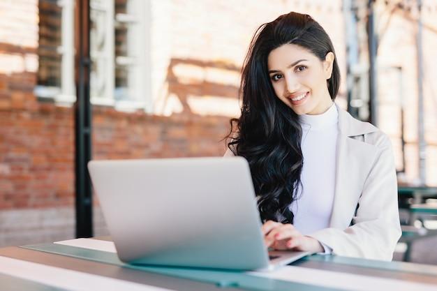 Attraktiver weiblicher blogger, der neuen schwierigen beitrag unter verwendung der modernen laptop-computers beim sitzen café am im freien schreibt