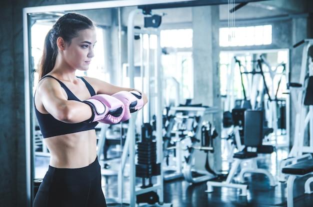 Attraktiver weiblicher boxer am training in der turnhalle