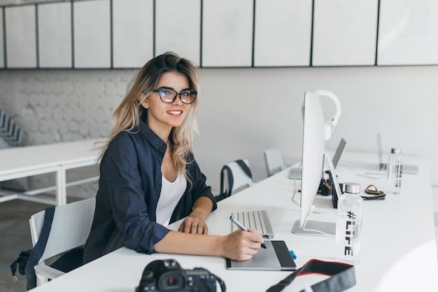 Attraktiver weiblicher designer, der tablette für arbeit verwendet und im büro mit hellem innenraum sitzt