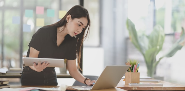 Attraktiver weiblicher freiberufler, der an dem projekt mit laptop arbeitet
