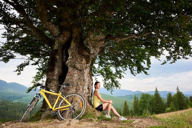 Attraktiver weiblicher radfahrer mit dem gelben gebirgsfahrrad, sonnigen tag in den bergen genießend