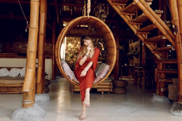 Attraktiver weiblicher standort in hängender bambustreppe auf freiluftveranda des hölzernen bungalows