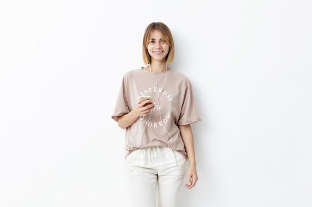 Attraktiver weiblicher teenager, der smartphone hält, musik oder hörbuch hört, während zur universität geht, glücklichen ausdruck habend