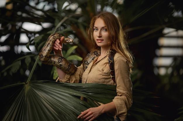 Attraktiver weiblicher tierpfleger mit pythonschlange in tropischer natur