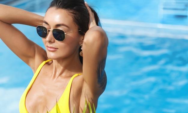 Attraktiver weiblicher tourist, der aus dem schwimmbad im kurhotel herauskommt, gelben bikini und sonnenbrille tragend, sonnenbaden in den sommerferien.