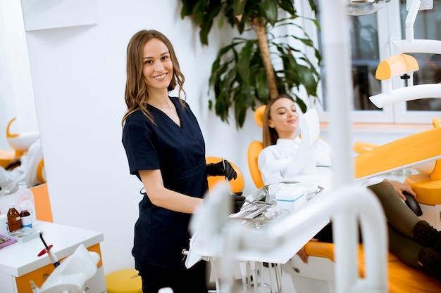 Attraktiver weiblicher zahnarztdoktor, der in ihrem büro, mit einer weiblichen patinette im stuhl steht