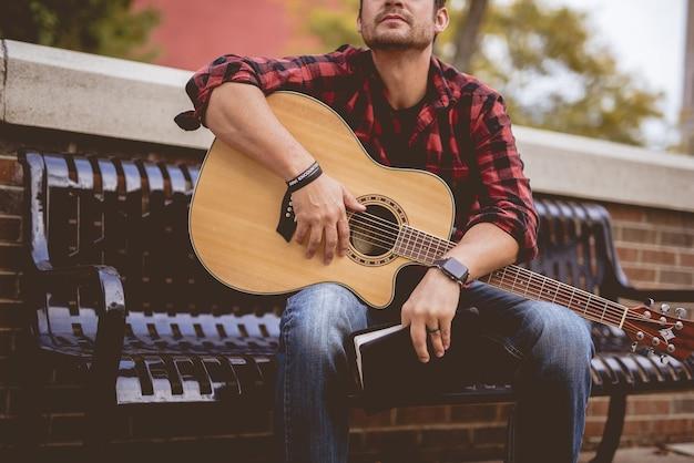 Attraktiver weißer mann, der auf einer bank sitzt, die die gitarre hält