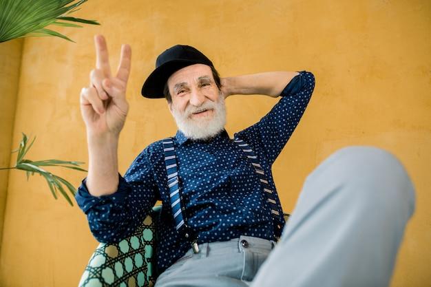 Attraktiver, zufriedener, selbstbewusster, stilvoller, bärtiger senior in trendiger kleidung und schwarzer hipster-mütze, der mit einer hand hinter dem kopf und einer anderen, die eine siegesgeste zeigt, vor der kamera posiert