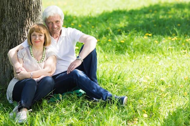 Attraktives älteres ehepaar, das zusammen unter dem baum auf der frühlingswiese sitzt