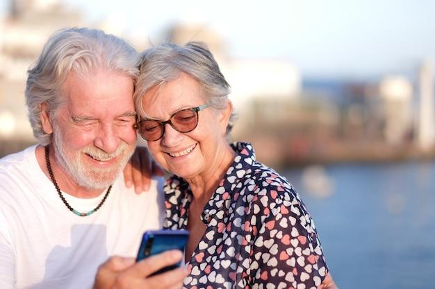 Attraktives älteres paar, das im freien auf see mit handy lächelt. kaukasisches paar weißhaarig