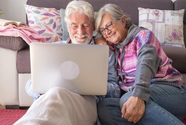 Attraktives älteres paar zu hause, das zusammen denselben laptop verwendet. lächelnder älterer rentner, der freizeit, technologie und soziale medien genießt