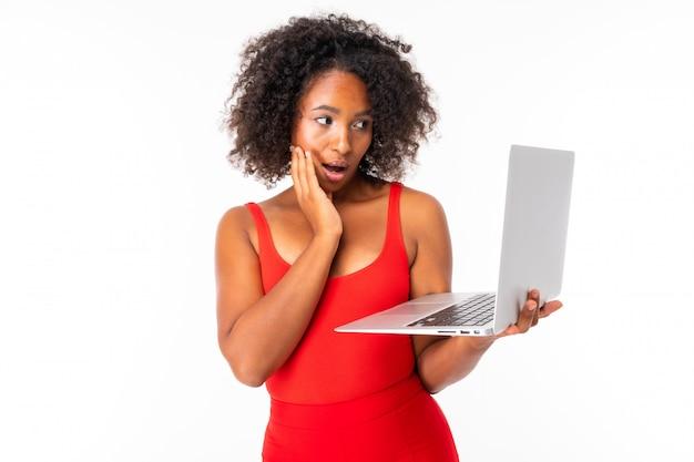 Attraktives afrikanisches mädchen, das einen offenen laptop hält und auf einer weißen wand überrascht schaut