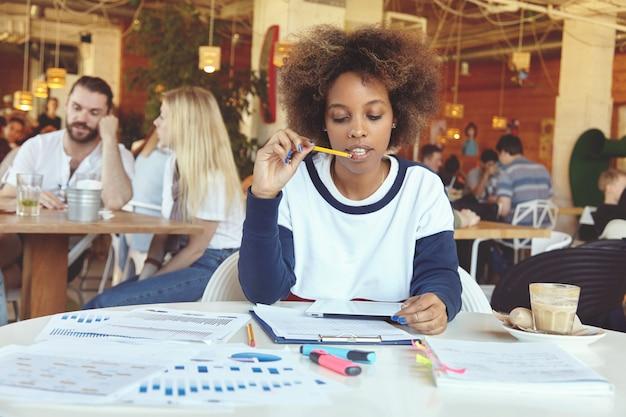 Attraktives afrikanisches studentenmädchen in der freizeitkleidung, die an der universitätskantine mit touchpad-pc sitzt, im internet surft, während man sich auf prüfungen vorbereitet, ihre lippen mit bleistift berührt und nachdenklich aussieht