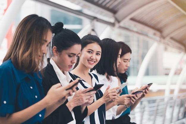 Attraktives asiatisches geschäftsfrauteam, das stadt des smartphone im freien spielt