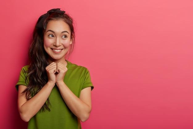 Attraktives asiatisches junges mädchen lächelt zärtlich, hält hände zusammen, begierig auf überraschung, grinst glücklich, schaut isoliert über rosa hintergrund beiseite