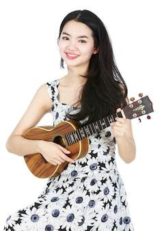 Attraktives asiatisches mädchen, das ukulele spielt