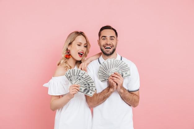Attraktives aufgeregtes junges paar, das zusammen über rosa steht und geldbanknoten zeigt