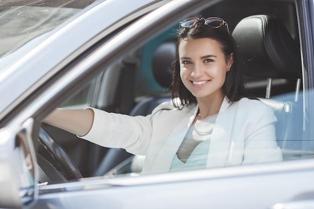 Attraktives autofahren der jungen frau. phantasie frau im automobil. reiche erwachsene frau im auto. zuversichtlich frau.