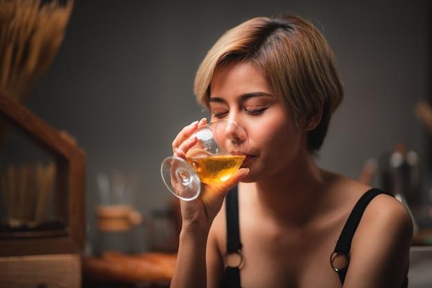 Attraktives barkeeper-mädchen, das in ihren händen frischen cocktail an der bartheke für feier hält