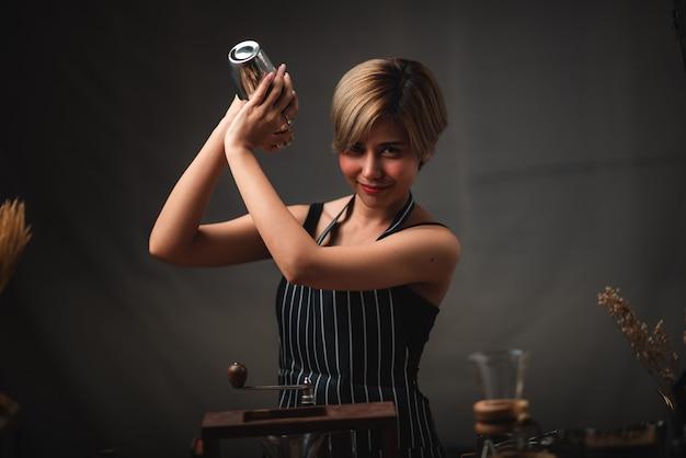 Attraktives barkeeper-mädchen, das in ihren händen stahlcocktailschüttler an der bartheke hält