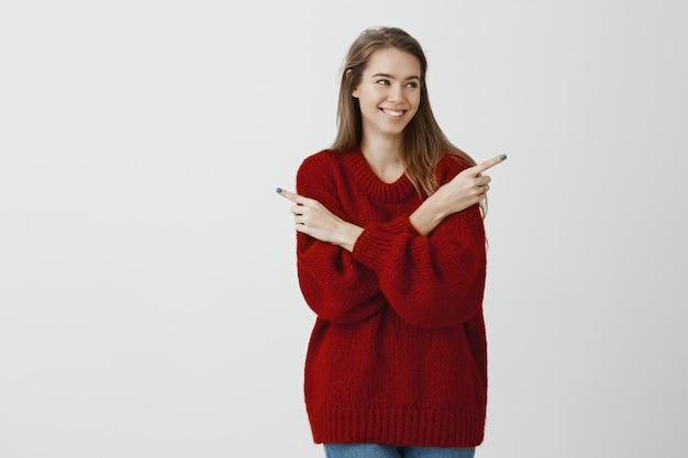 Attraktives beliebtes mädchen, das entscheidung über welches datum trifft. erfreute freudige kaukasische frau im roten losen trendigen pullover, der nach rechts schaut und in verschiedene richtungen zeigt und mit breitem lächeln zögert