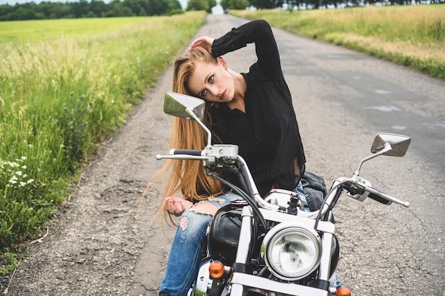 Attraktives biker-mädchen schaut in einen rückspiegel ihres motorrades