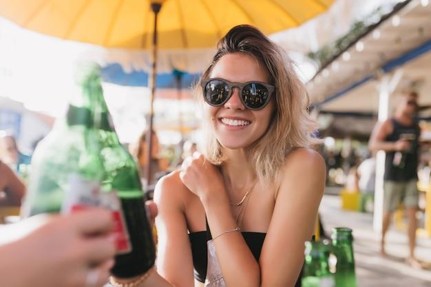 Attraktives blondes mädchen, das bier im café trinkt und lacht. aufgeregte junge frau, die zeit mit freund im restaurant im freien am sommertag verbringt.