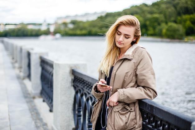 Attraktives blondes mädchen, das entlang die promenade geht und musik mit kopfhörern hört.
