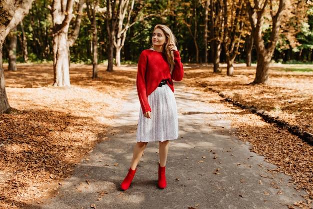 Attraktives blondes mädchen, das in den trendigen kleidern im herbstpark aufwirft. junge frau, die roten pullover und weißen rock im freien trägt.