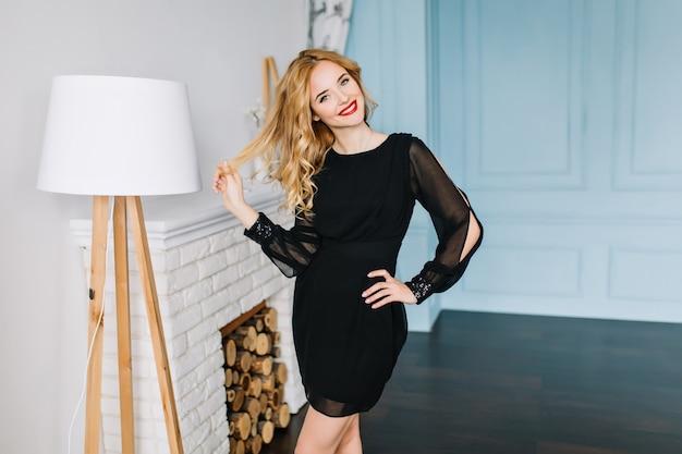 Attraktives blondes mädchen im raum mit weißer, türkisfarbener wand, genießen, posieren, lächeln, ihr langes gewelltes haar berühren. tragen von leichtem make-up mit rotem lippenstift, schönes schwarzes kleid.