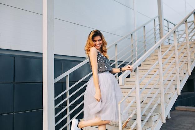 Attraktives blondes mädchen im tüllrock, der spaß auf treppen hat. sie lächelt nach unten.