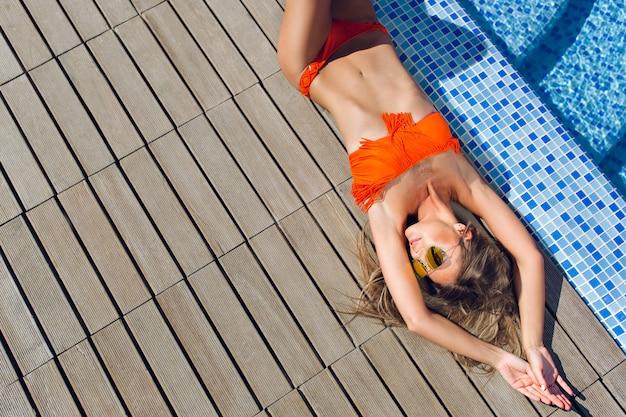 Attraktives blondes mädchen mit langen haaren liegt auf flor nahe pool. sie hält die hände oben und schaut zur seite. sicht von oben.