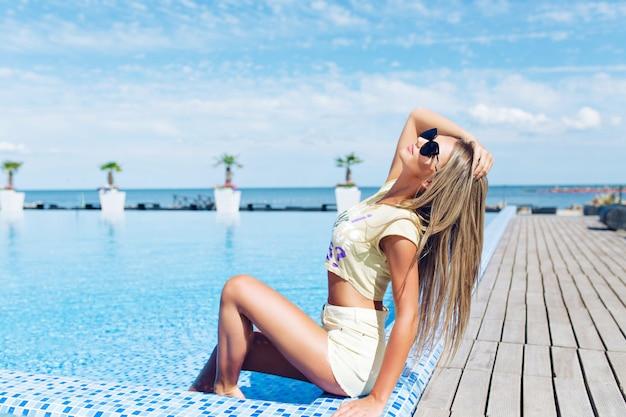 Attraktives blondes mädchen mit langen haaren sitzt in der nähe des pools. sie posiert und schaut nach oben.