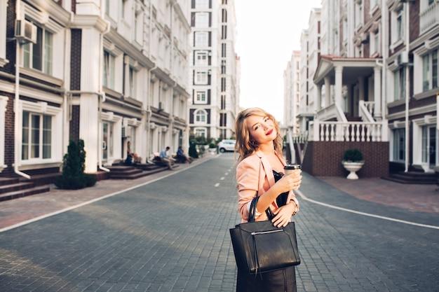 Attraktives blondes mädchen mit weinigen lippen, die mit tasse kaffee in der korallenjacke auf straße gehen. sie trägt eine schwarze tasche