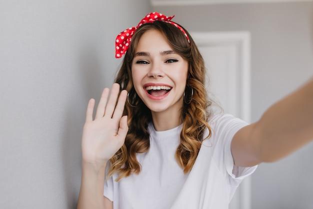 Attraktives brünettes mädchen, das zu hause mit fröhlichem lächeln aufwirft. bezauberndes europäisches weibliches modell in ohrringen, die selfie machen.