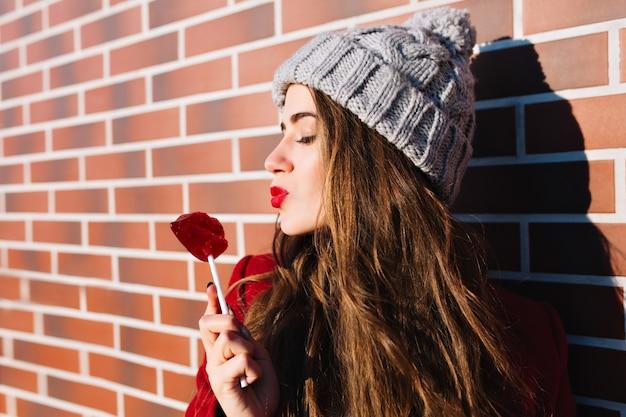 Attraktives brünettes mädchen des nahaufnahmeporträts mit langen haaren an der wand draußen. sie trägt eine strickmütze, hält die augen geschlossen und schickt einen kuss auf die roten lippen des lutschers.
