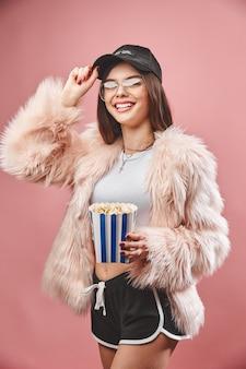 Attraktives brünettes mädchen in rosa kunstpelz, das popcorn in der hand hält und in schwarzen shorts weißes top trägt ...