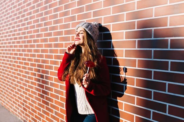Attraktives brünettes mädchen mit langen haaren an der wand draußen. sie trägt eine strickmütze und einen roten mantel. hält lollipop rote lippen. mit geschlossenen augen zum sonnenschein lächeln.