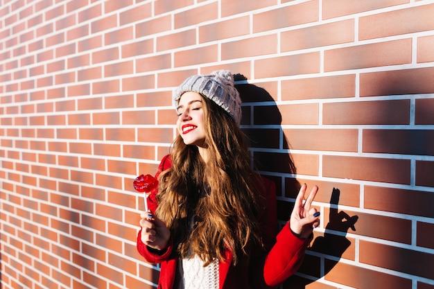 Attraktives brünettes mädchen mit langen haaren im roten mantel, der auf sonnenschein an der wand draußen kühlt. sie trägt eine strickmütze und hält lutscherrote lippen.